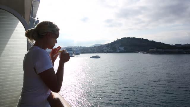 woman sips tea while watching boat enter port, kusadasi, turkey - nautical vessel stock videos & royalty-free footage