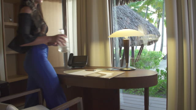 a woman sits at a desk in her hotel room to write a postcard. - territori francesi d'oltremare video stock e b–roll