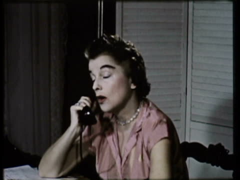 stockvideo's en b-roll-footage met 1955 ms woman sits at desk answering on phone / usa - 1955