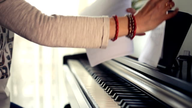stockvideo's en b-roll-footage met woman sits at the piano, places the music sheets and to start playing - una sola mujer