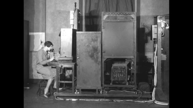 woman sits down at desk and talks on telephone next to metal cabinets / door of one cabinet open revealing machine inside that telephone is connected... - bländare bildbanksvideor och videomaterial från bakom kulisserna