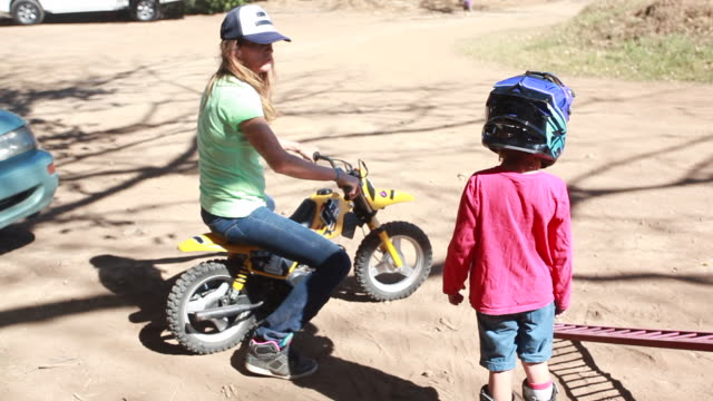 a woman sits down on a young boys dirt bike as the young boy wearing a helmet talks to her - kelly mason videos stock videos & royalty-free footage