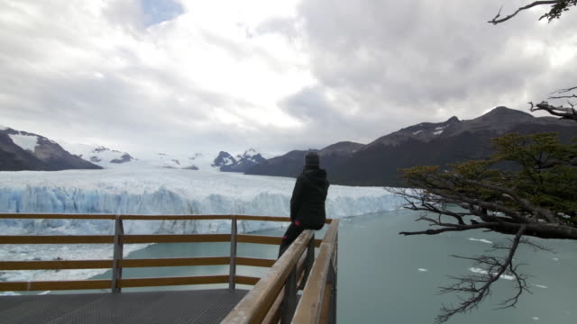 woman sits in a wall looking at the glacier - argentina stock videos and b-roll footage