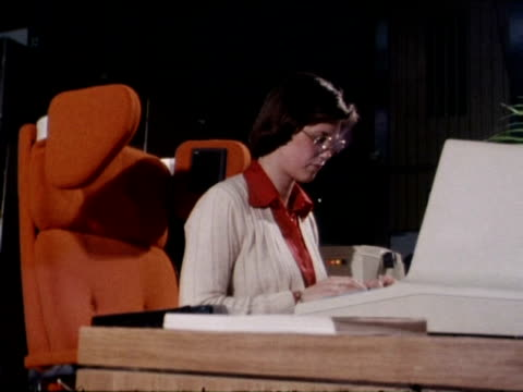 Woman sits in armchair using new word processor and floppy disc 1977