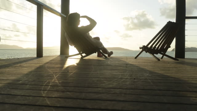woman sits in chair on wooden deck looking out to sea. - chair stock videos and b-roll footage
