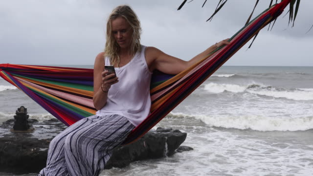 woman sits in hammock above surf, sends text on smart phone - pants stock videos and b-roll footage