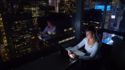 CLOSE UP: Woman sits in her hotel room above Times Square and works on laptop