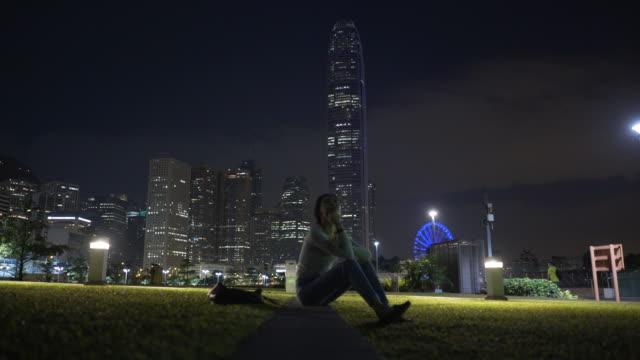 vidéos et rushes de woman sits in park under hong kong skyline - main au menton