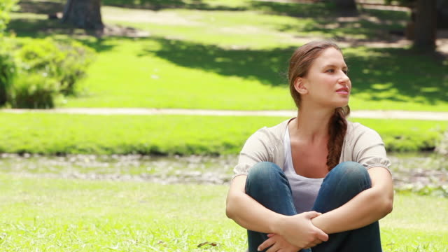 A woman sits on the ground and then her friend joins her as they look upwards