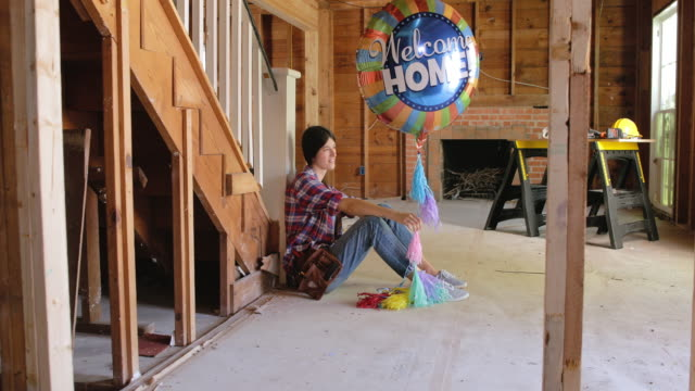 """a woman sits inside her home renovation holding a """"welcome home"""" balloon. - welcome stock videos and b-roll footage"""