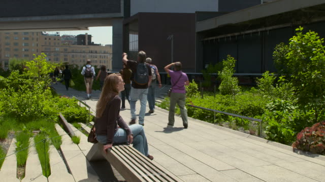 Woman sits on a bench on the Highline park in New York.  People walk past.
