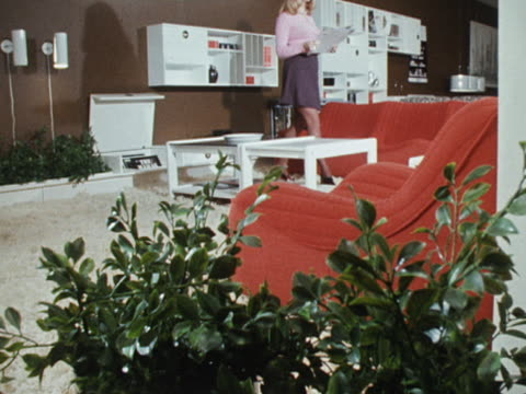 stockvideo's en b-roll-footage met a woman sits on a modern red sofa at a furniture exhibition at earls court - koffietafel