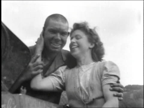 vidéos et rushes de woman sits on american tank during world war ii and kisses soldier on the cheek / france - film documentaire image animée