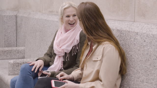 Woman sits on bench in city, friend meets up and they chat and laugh together.