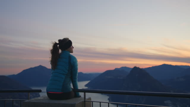 woman sits on edge of railing on mountain top overlooking lake and mountains - standing water stock videos & royalty-free footage