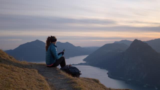 vidéos et rushes de la femme s'assied sur le bord du sentier utilisant la tablette numérique sur le dessus de la montagne - activity