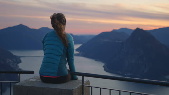 woman sits on edge railing overlooking sunset and view of lake and mountains below - mid adult women stock videos & royalty-free footage