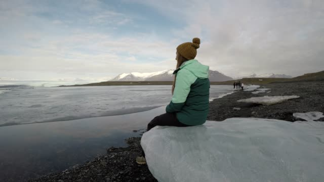 woman sits on iceberg and looks out at glacial lake - cappotto invernale video stock e b–roll