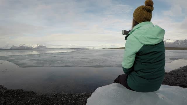 frau sitzt auf eisberg und telefon foto von gletschersee - einzelne frau über 30 stock-videos und b-roll-filmmaterial
