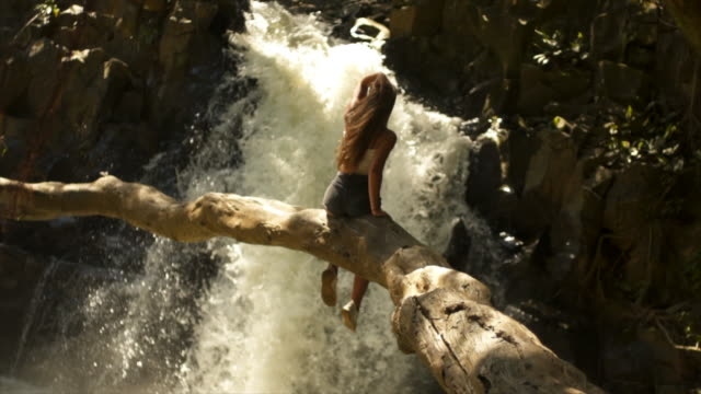 woman sits on log looking out at waterfall - generation z stock videos & royalty-free footage