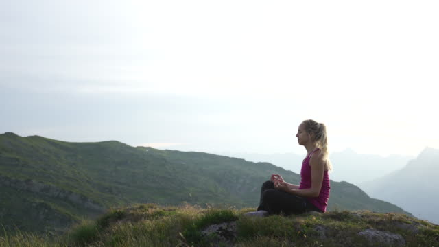 vídeos de stock e filmes b-roll de woman sits on mountain doing yoga at sunset - cabelo louro