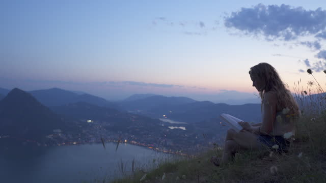 woman sits on mountain top after sunset reading book, looks out at view of lake - fairytale stock videos & royalty-free footage