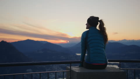 woman sits on railing overlooking sunset and view of lake and mountains below - mid adult women stock videos & royalty-free footage
