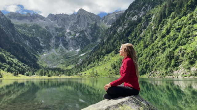 woman sits on rock on alpine lake meditating, yoga, relaxing breathing in fresh air of nature - nature stock videos & royalty-free footage