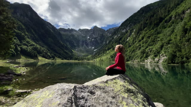 woman sits on rock on alpine lake meditating, yoga, relaxing breathing in fresh air of nature - switzerland stock videos & royalty-free footage