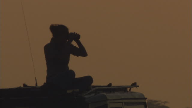 a woman sits on top of a truck and looks through binoculars, then opens a laptop. - binoculars stock videos & royalty-free footage