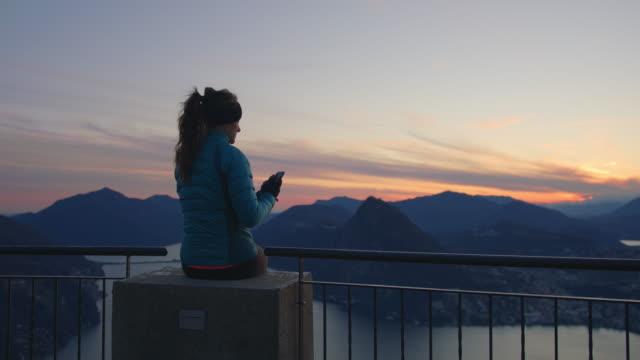 vidéos et rushes de la femme s'assied au-dessus de la montagne au coucher du soleil utilisant le smartphone - s'évader du réel