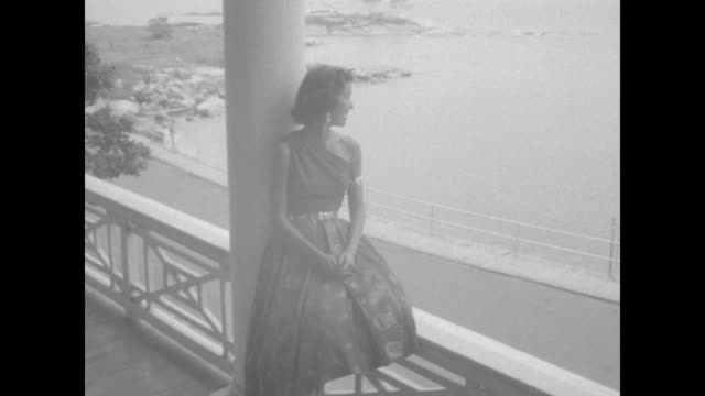 woman sits on veranda railing with lakeshore view and gazes out at water while sometimes turning toward camera during fashion shoot at the griswold... - groton connecticut stock videos & royalty-free footage