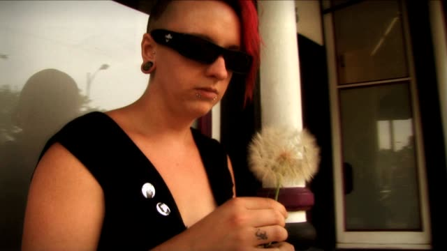 stockvideo's en b-roll-footage met a woman sits outside a storefront and blows at a dandelion. - hanenkam haardracht