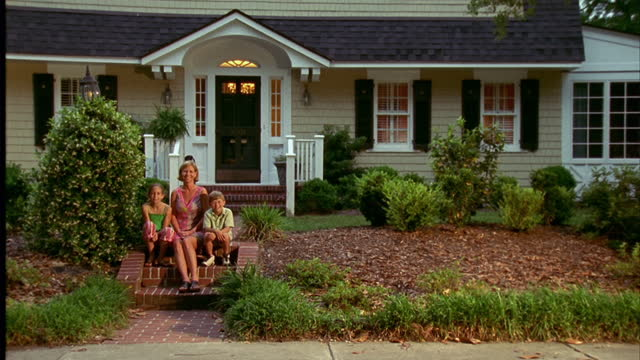 a woman sits with her children on steps in front of suburban house. - veranda stock videos & royalty-free footage