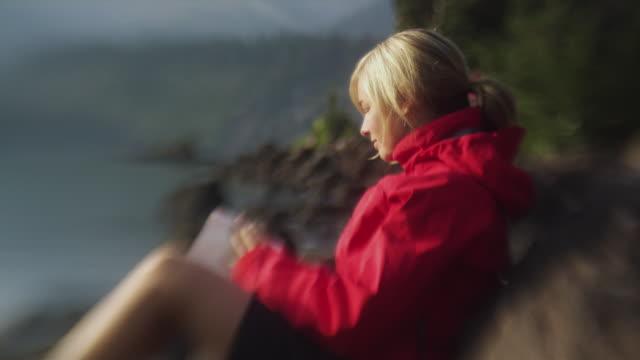 ms selective focus woman sitting against rock writing in diary, garibaldi provincial park, squamish, british columbia, canada - garibaldi park stock videos & royalty-free footage