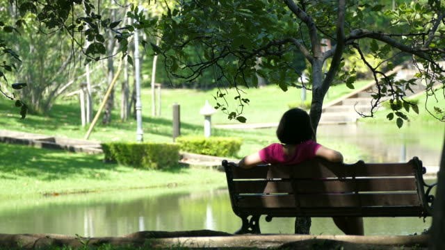 woman sitting alone in garden - weekend activities stock videos & royalty-free footage