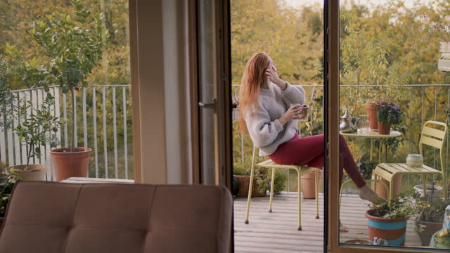 woman sitting alone on balcony at home - young women stock-videos und b-roll-filmmaterial