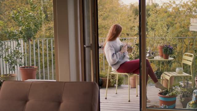 woman sitting alone on balcony at home - sofa bildbanksvideor och videomaterial från bakom kulisserna