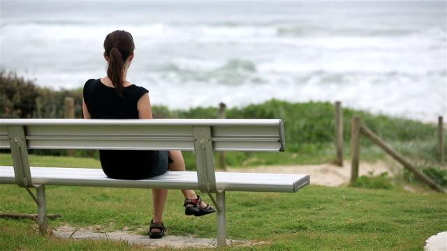 vídeos de stock e filmes b-roll de isolado mulher sentada no banco e olhando para o mar, na austrália - banco de parque