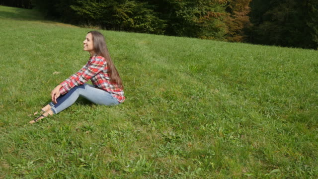 Woman sitting and admiring the nature on a sunny, cloudless day