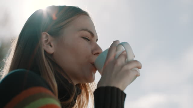 vídeos de stock e filmes b-roll de woman sitting and drinking coffee on camping trip by the lake - chávena