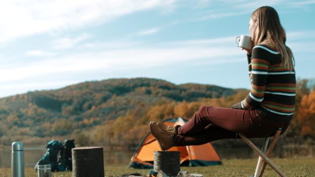 frau, sitzen und kaffee trinken, auf camping-ausflug am see - tasse oder becher stock-videos und b-roll-filmmaterial