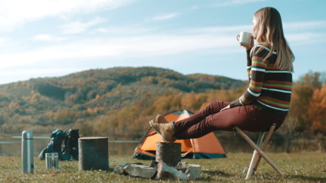 Woman sitting and drinking coffee on camping trip by the lake