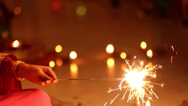 ms woman sitting and enjoying sparklers in diwali festival - 部分点の映像素材/bロール