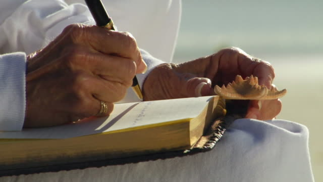 cu woman sitting and hold starfish as she writes in journal/ tu woman looking down/ td woman writing/ sycamore cove, california  - 日記点の映像素材/bロール