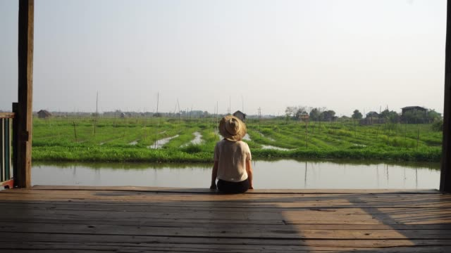 woman sitting and looking at floating gardens on inle lake - myanmar stock videos & royalty-free footage