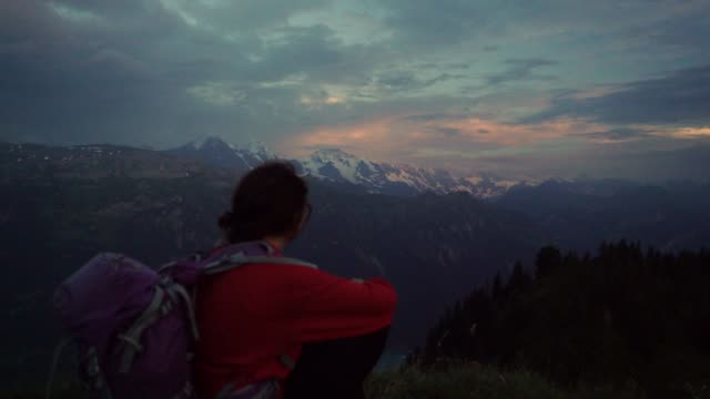 frau sitzt und schaut auf den sonnenuntergang über den schweizer alpen - gegensatz stock-videos und b-roll-filmmaterial