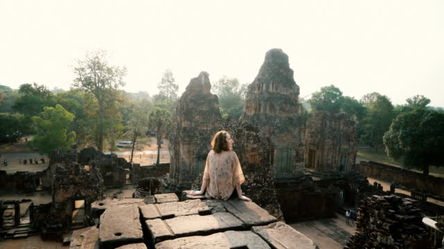 Woman sitting  and looking at view  in Angkor Temple in Cambodia