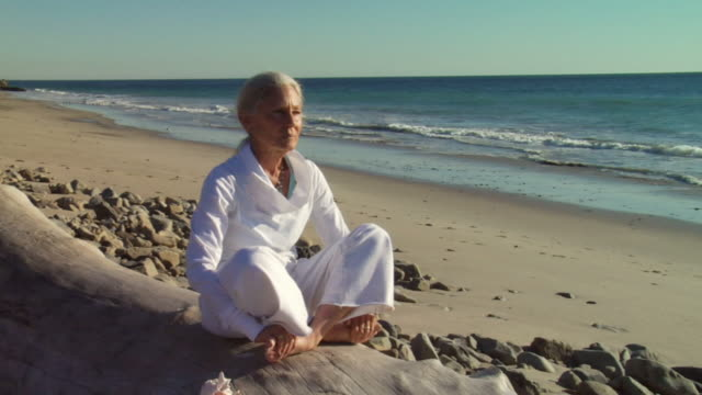 ms woman sitting and meditating on beach log with ocean tide in background/ sycamore cove, california - seniorinnen stock-videos und b-roll-filmmaterial