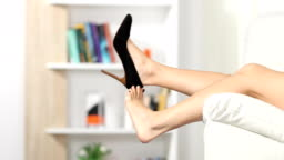 Woman sitting and rests taking off shoes on a couch